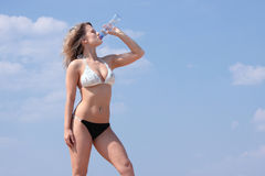 Young woman in bikini drinking water Stock Photography