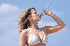 Young woman in bikini drinking water Stock Photos