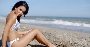 Young woman in a bikini enjoying a day at the sea. Side sitting on a tropical beach close to the ocean sunbathing and turning to look at the camera stock footage