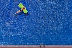 Young woman in bikini. Enjoying suntan. Vacation concept. Top view of slim young woman in bikini on the green air mattress in the big swimming pool Royalty Free Stock Photo