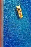 Young woman in bikini. Enjoying suntan. Vacation concept. Top view of slim young woman in bikini on the yellow air mattress in the big swimming pool Royalty Free Stock Images