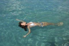 Young woman in bikini floating in water Stock Photography