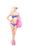 Young woman in bikini holding a pink bag Stock Photography