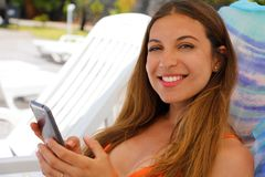 Young woman in bikini holding smartphone and looking at camera. Beautiful girl using mobile phone at beach. Smiling brunette woman. Enjoying at beach while royalty free stock photos