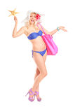 Young woman in bikini holding a starfish and bag stock photo