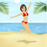 Young woman in bikini jumping in the air on tropical beach Stock Photography