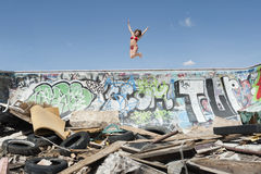 Young woman in bikini jumping over graffiti wall with garbage in foreground Stock Photography