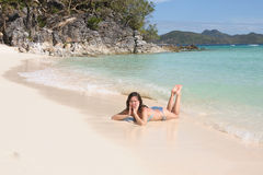 Young woman in bikini laying on the beach Stock Images