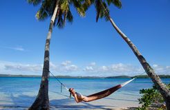 Young woman in bikini laying in a hammock between palm trees, Of Royalty Free Stock Image