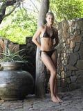 Young Woman In Bikini Leaning on Tree Trunk Stock Photo