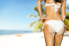 Young woman in bikini looking at beach. With sand on her body, shot from behind Stock Images