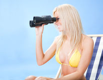 Young woman in bikini looking through binoculars Royalty Free Stock Image