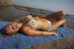 Young woman in bikini lying. On the beach Stock Image