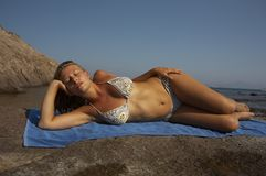 Young woman in bikini lying. On the beach Stock Photography