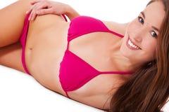 Young woman in bikini lying on the floor Stock Photography