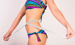 Young woman in bikini measuing her waist Royalty Free Stock Photography