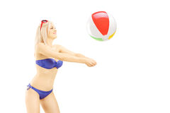Young woman in bikini playing with a beach ball. Isolated on white background Royalty Free Stock Photos