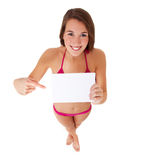 Young woman in bikini pointing at blank sign Stock Photos