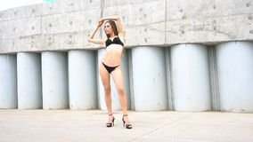 Young woman in bikini is posing on background of concrete wall stock footage
