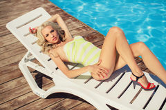 A young woman in a bikini posing by the pool Royalty Free Stock Photo