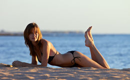 Young woman in bikini posing on sea coast Royalty Free Stock Images
