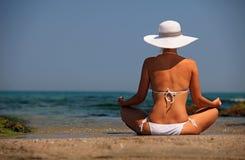Young woman in bikini relaxing on beach. Back view Stock Image
