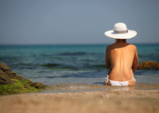 Young woman in a bikini relaxing on a beach. Rear view Stock Photos