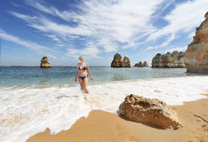 Young woman in bikini  at Rocky beach at sunset, Lagos, Portugal. Counter light Royalty Free Stock Images