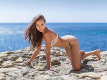 Young woman in bikini on rocky seashore Stock Photo