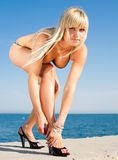 Young woman in bikini on seashore. Attractive young long-haired blond woman at the sea Royalty Free Stock Image
