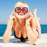 Young woman in bikini on seashore. Young blond woman looks at camera through a sunglasses Stock Photography