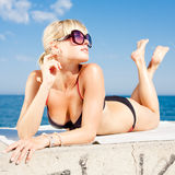 Young woman in bikini on seashore. Attractive young long-haired blond woman in sunglasses at the sea Royalty Free Stock Image