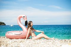 Young woman with bikini sitting close to giant inflated flamingo on a beach with turquois water of Ionian Sea Albania. Young woman with bikini sitting close to stock photography