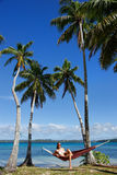 Young woman in bikini sitting in a hammock between palm trees, O Stock Photography