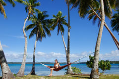 Young woman in bikini sitting in a hammock between palm trees, O Royalty Free Stock Photography
