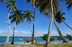 Young woman in bikini sitting in a hammock between palm trees, O Royalty Free Stock Image