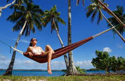 Young woman in bikini sitting in a hammock between palm trees, O Stock Photo