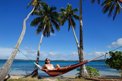 Young woman in bikini sitting in a hammock between palm trees, O Royalty Free Stock Photos
