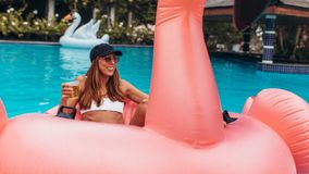 Woman enjoying at pool party. Young woman in bikini sitting relaxed on inflatable pool toy and having beer. Woman enjoying at pool party with beer Stock Photography