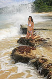 Young woman in bikini sitting on rocks at Rincon beach, Samana p Royalty Free Stock Images
