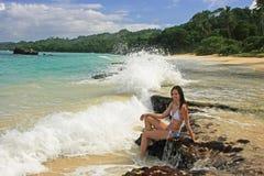 Young woman in bikini sitting on rocks at Rincon beach, Samana p Stock Image