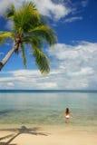 Young woman in bikini standing in clear water, Nananu-i-Ra islan Stock Photo