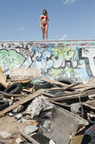 Young woman in bikini standing on graffiti wall with garbage in foreground Stock Image