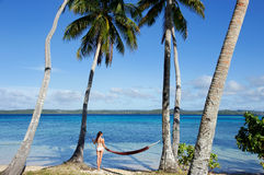 Young woman in bikini standing by the hammock between palm trees Royalty Free Stock Image