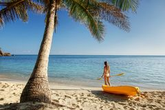 Young woman in bikini standing on a sandy beach with sea kayak and paddle. Nacula Island, Fiji royalty free stock photos