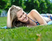 Young woman in bikini sunbathing - summer. Sexy young woman in bikini sunbathing outside on a blue towel sunbathing - lying on her stomach - smiling Royalty Free Stock Image