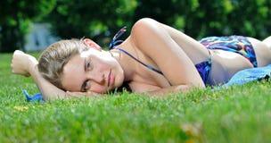 Young woman in bikini sunbathing - summer. Sexy young woman in bikini sunbathing outside on a blue towel sunbathing - lying on her stomach Royalty Free Stock Image