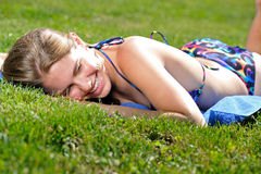 Young woman in bikini sunbathing - summer. Sexy young woman in bikini sunbathing outside on a blue towel sunbathing - lying on her stomach - smiling Stock Images