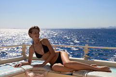 Young woman in bikini sunbathing on yacht Stock Image