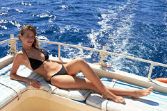 Young woman in bikini sunbathing on yacht Stock Photography